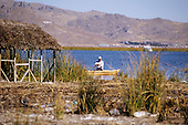 Lake Titicaca, Peru. Man in a reed boat at the floating island of Uros near a partly built house.
