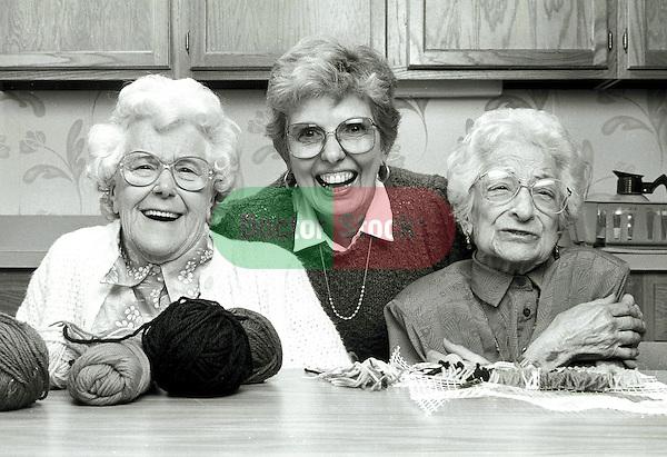 portrait of three elderly women sitting in kitchen laughing