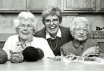 portrait of three elderly women sitting in kitchen laughing