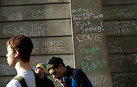 Demostrators pass graffiti on the wall of the Bank of England as thousands of protestors descended on the City of London ahead of the G20 summit of world leaders to express anger at the economic crisis, which many blame on the excesses of capitalism.