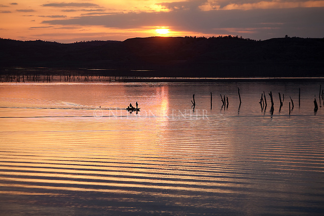 Fishermen in a boat on the Missouri River above Fort Peck Reservoir in Montana as the sun sets behind the ridge