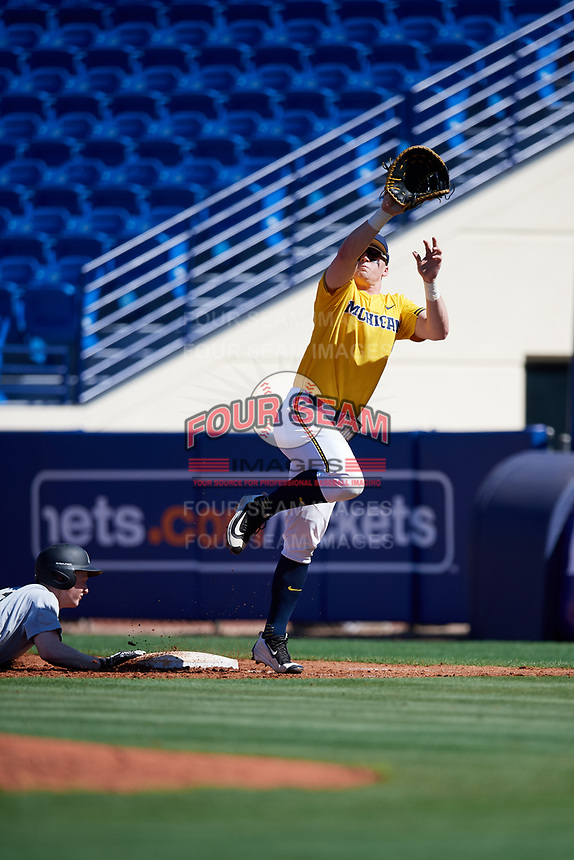 Michigan Wolverines first baseman Jesse Franklin (7) jumps for an errant throw during a game against Army West Point on February 17, 2018 at Tradition Field in St. Lucie, Florida.  Army defeated Michigan 4-3.  (Mike Janes/Four Seam Images)