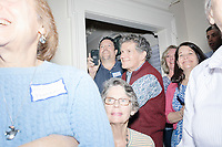 People watch as Democratic presidential candidate and South Bend mayor Pete Buttigieg speaks at a house party with the Bedford Democrats in Bedford, New Hampshire, on Sat., Apr. 20, 2019. The candidate stood on a chair throughout his speech.