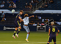 KANSAS CITY, KS - OCTOBER 11: #25 Walker Zimmerman of Nashville SC and #27 Gianluca Busio of Sporting Kansas City battle to head the ball during a game between Nashville SC and Sporting Kansas City at Children's Mercy Park on October 11, 2020 in Kansas City, Kansas.