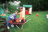Little boy & dad playing in garden in home yard with wheelbarrow of dirt, having fun on lawn digging with dirt, laughing - quality parenting time
