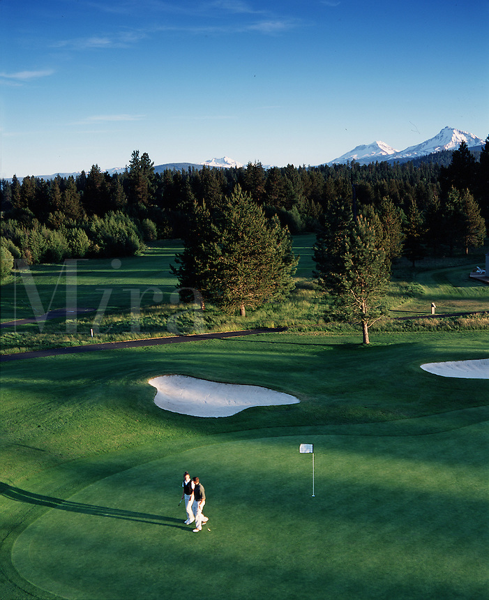 Overview of golfer hitting out of a sand bunker on the 18th hole on the Big Meadows Course. Black Butte Ranch, Oregon.