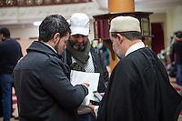 Imam Mohamed Taha Sabri von der Dar Assalam Moschee . Der Imam leitet auch die Neukoellner Begegnungsstaette e.V.. Fuer seine engagierte Arbeit bekam er 2015 den Verdienstordens des Landes Berlin verliehen.<br /> Im Bild: Viele Gottsdienstbesucher suchen nach dem Freutagsgebet den Rat des Imam. Laut Aussage des Imam sind ca. 80 Prozent der Menschen Fluechtlinge aus der nahe gelegenen Massenunterkunft im ehemeligen Flughafen Tempelhof. Hier braucht ein Fluechtling Rat bei einem Dokument der Auslaenderbehoerde.<br /> 26.2.2016, Berlin<br /> Copyright: Christian-Ditsch.de<br /> [Inhaltsveraendernde Manipulation des Fotos nur nach ausdruecklicher Genehmigung des Fotografen. Vereinbarungen ueber Abtretung von Persoenlichkeitsrechten/Model Release der abgebildeten Person/Personen liegen nicht vor. NO MODEL RELEASE! Nur fuer Redaktionelle Zwecke. Don't publish without copyright Christian-Ditsch.de, Veroeffentlichung nur mit Fotografennennung, sowie gegen Honorar, MwSt. und Beleg. Konto: I N G - D i B a, IBAN DE58500105175400192269, BIC INGDDEFFXXX, Kontakt: post@christian-ditsch.de<br /> Bei der Bearbeitung der Dateiinformationen darf die Urheberkennzeichnung in den EXIF- und  IPTC-Daten nicht entfernt werden, diese sind in digitalen Medien nach §95c UrhG rechtlich geschuetzt. Der Urhebervermerk wird gemaess §13 UrhG verlangt.]