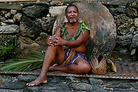 The Chief in his village during the very traditional Yap Day  leaning on the famous Yap Stone Money during Yap Day, Yap Micronesia