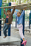 Two 7 year old girls hanging from climbing equipment at the playground