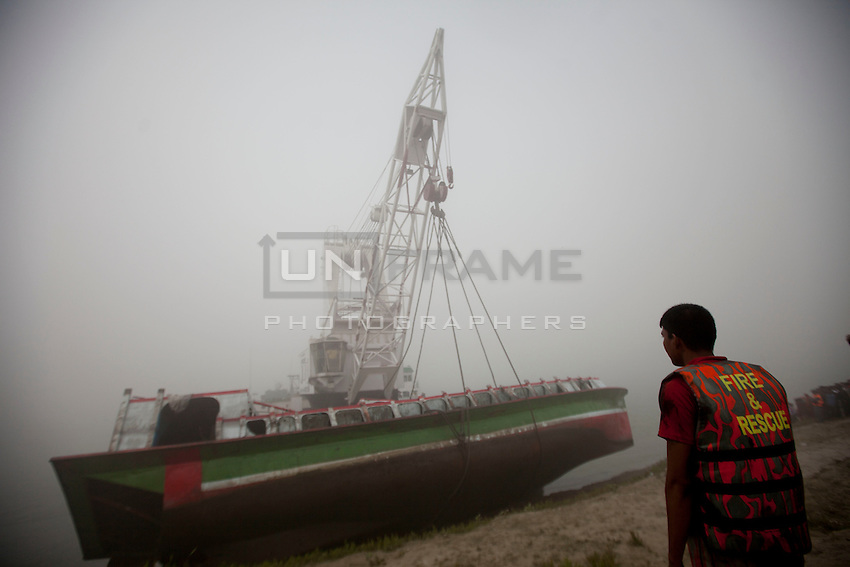 Bangladeshi rescue workers attempt to lift the wreckage of a ferry that capsized in the River Padma  after being hit by a cargo vessel at Paturia , in Manikganj district, about 80 kilometers northwest of Dhaka, Bangladesh. Feb. 23, 2015
