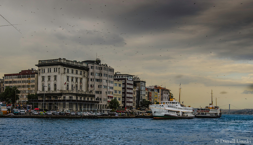 Fine Art Landscape Photograph. The Bosphorus Strait in Istanbul, Turkey. The dramatic lighting on the buildings and the birds flying overhead create the mood of this print. <br />