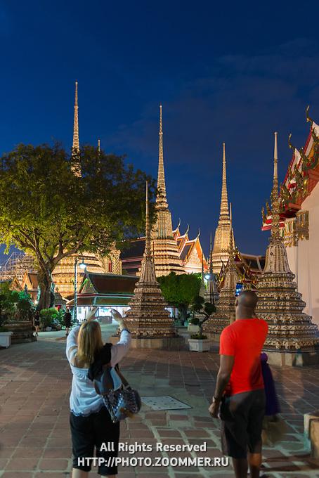 Tourists take photos of buddist temple Phra Maha Chedi at night, Bangkok, Thailand