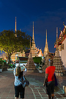 Tourists take photos of buddist temple Phra Maha Chedi at night, Bangkok, Thailand