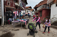 Serbia. Leskovac is a city and the administrative center of the Jablanica District in southern Serbia. Romani neighborhood. A Roma mother with her daughter and her son seated in a stroller. A market shop is selling children's clothes on the road. A T-shirt (or t shirt, or tee) is a style of unisex fabric shirt named after the T shape of its body and sleeves. The Romani (also spelled Romany) or Roma, Roms or Gypsies, are a traditionally itinerant ethnic group. 18.4.2018 © 2018 Didier Ruef for the Pestalozzi Children's Foundation