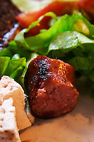 A dish of typical Uruguay barbecue with chicken, pork, beef, sausages, sweetbread, blood sausages and more in a restaurant along the coast in Montevideo. Close-up of a piece of grilled sausage, salad and cheese. at the restaurant La Estacada on the waterside Montevideo, Uruguay, South America