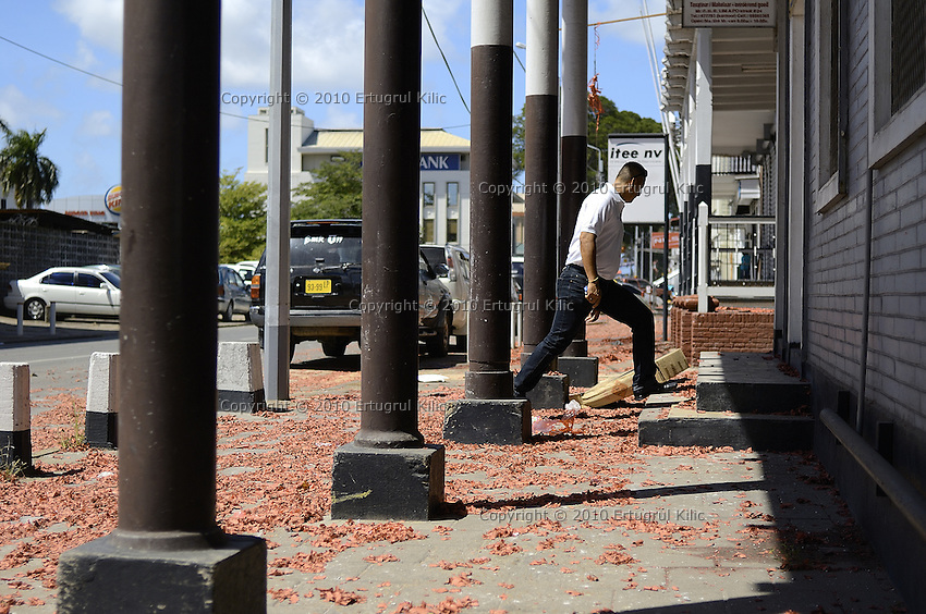 A worker enters to his office while jumping on billions of small red cartons, rest of long firecrackers lays on the streets, sidewalks.....End of year 2010 celebrations on the streets of Paramaribo. Suriname is one of biggest consumer in South America that using firecrackers, fireworks ( also locally known as pagara ) for celebrations, especially for end of every years and also beginning of every new Chinese Years.