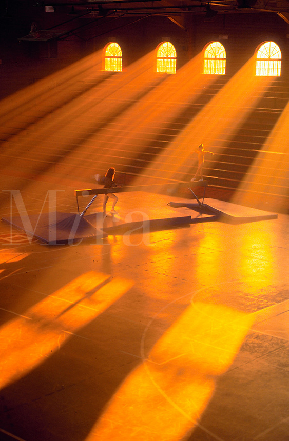 Sunlight pours through windows of gym while a young girl practices on a balance beam with her coach watching.