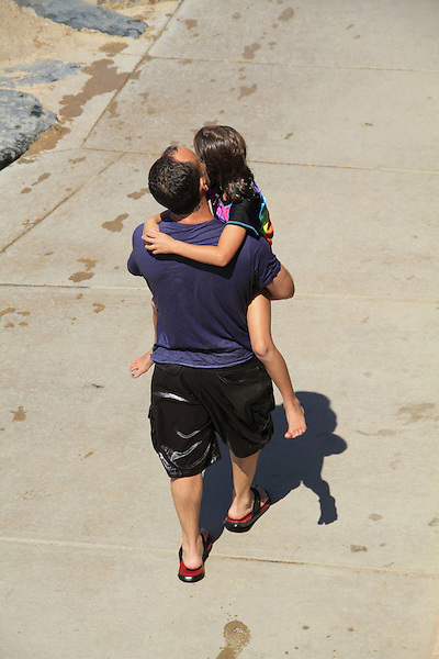 Father carries daughter after swimming in Boulder, Colorado. .  John offers private photo tours in Denver, Boulder and throughout Colorado. Year-round Colorado photo tours.
