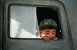 Chinese boy looking out window of train, China