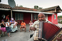RUMAENIEN, 08.2010, Barbulesti. © Bogdan Croitoru/EST&OST. Aus Frankreich abgeschobene Roma-Wirtschaftsfluechtlinge zurueck in der Heimat: Costache Ionel nicknamed Merisor shows his skills in playing the accordion watched by his family in his house yard in Barbulesti village. He used to be a street player in Grenoble, France. Mister Costache, his wife, daughter and other relatives were returned to Romania by French authorities.