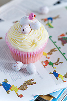 Small hard-shelled chocolate eggs sit in a nest of icing on top of a cup cake