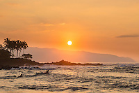Two surfers paddle over the waves on their way out to the break at sunset, North Shore, O'ahu.