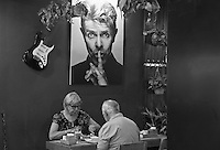 A poster of David Bowie and Tourist eating out at night in Hanoi, the capital of Vietnam, is known for its centuries-old architecture and a rich culture with Southeast Asian, Chinese and French influences. At its heart is the chaotic Old Quarter, where the narrow streets are roughly arranged by trade. There are many little temples, including Bach Ma, honoring a legendary horse, plus Đồng Xuân Market, selling household goods and street food.