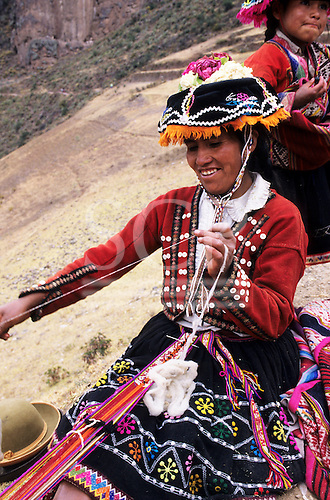 Pisac, Peru. Smiling woman in traditional dress spinning wool and weaving a strap using a foot loom.