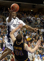 University of Connecticut forward Denham Brown (L) drives over University of Albany forward Brent Wilson (R) in the first half of play during the first round of the men's NCAA Tournament in Philadelphia, March 17, 2006. REUTERS/Bradley C Bower
