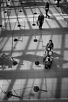 """Switzerland. Geneva. Men and women standing in the hall of Planète Charmilles which  is a large shopping center.  A mother is pushing a stroller with her child. A man is reading the latest news on his smartphone. Lights and shadows. The two lines indicate the way people have to walk due to the Coronavirus pandemic.Due to the spread of the Coronavirus (also called Covid-19), the Federal Council has categorised the situation in the country as """"extraordinary"""". From March 16 the government ramped up its response to the widening pandemic, ordering the closure of non essential shops. From April 27, they can reopen under very tight conditions. Social distancing and masks. 12.06.2020  © 2020 Didier Ruef"""