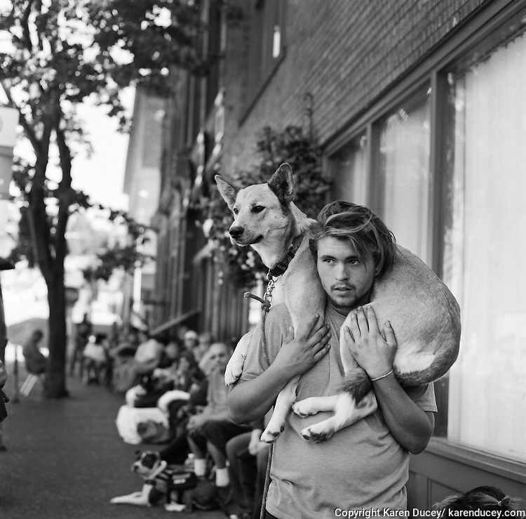 """Dillon Green, from Seattle, Wash. holds his dog, Katara, on his shoulders while he waits in line with over a hundred other people and their pets at the Doney Memorial Pet Clinic outside the Union Gospel Mission.  Green got Katara as a one-month old puppy from his sister.  He sleeps under a bridge with friends. He is upset with the county animal control service who gave him a ticket for letting Katara run off leash in a park. He says he can't fight the ticket because there is a warrant out for arrest, but he can't afford to pay it either. They came to the Doney Clinic to get Katara some shots after she was bitten by a rat the day before.  When he needs to punish her Green says he holds her snout shut and bites her over the nose when she is bad """"which is all the time."""" He says """"She has to be well behaved because I'm homeless and I can lose her if she misbehaves."""""""