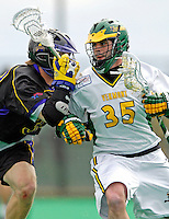 14 April 2007: University of Vermont Catamounts' Sean Layton, a Senior from Wilmington, MA, is checked by University of Albany Great Danes' Mike Ammann at Moulton Winder Field, in Burlington, Vermont. The Great Danes defeated the Catamounts 14-7...Mandatory Photo Credit: Ed Wolfstein Photo