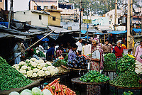 Fresh produce and shoppers in a typical scene at a vegetable market, India