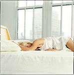 Woman in bed with windows in background