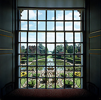 View through a window over an ornamental lake at Easton Neston and the manicured gardens beyond