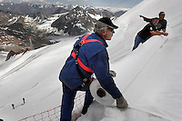 "Workers prepare to unroll uncovered fleece-like material and attached it to the top of the part of the glacier. Brunnenkogel Ferner (Austrian word for glacier) is wrapped with a cover to keep it from melting.   Covered ice melts slower. <br /> The ski area at 3,400 meters is covered to help save the ski industry since the glacier is retreating.  The cost of materials is one Euro per square meter.<br /> <br /> The Alpine glaciers -- in Austria, Switzerland, France and Italy -- are losing one percent of their mass every year and, even supposing no acceleration in that rate, will have all but disappeared by the end of the century. More hot, dry summers like that of 2003 in Europe, when the loss speeded to five percent, could cut the life expectancy to no more than 50 years, according to Wilfried Haeberli of the University of Zurich...""We estimate that by the end of the 21st century, with a medium-type climate scenario, about five percent of what existed in the 1970s will have survived, he added."
