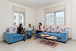 """April 2018. Muna, 27 (on the left) and her new flatmate Sawsan, 33 (on the right). The two women work in the """"Q center"""", the open air mall located at the heart of the city, and live in rented apartment. The two women, who present themselves as ambitious and independent woman know each-other from university. Muna says she appreciate that women can find opportunities in Rawabi. Their work represent most of their life occupation, there is no much time left out of working time, only to appreciate a glass of wine after a working day."""