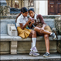 Faces Of Cuba - School girls texting. It's universal now.<br />