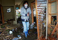 A lady returns to her house to retrieve what-ever belongs she is able to find. Personal belongs were the greatest loss with people returning looking for momentos of loved ones lost photo albums, pictures and family heirlooms. .16 Mar 2011