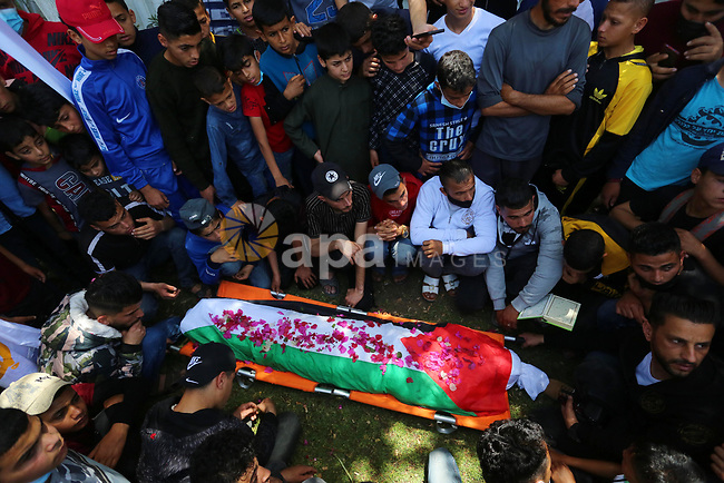 """Relatives of the Palestinian Yousef Abu Jazar, mourn during his funeral, in Rafah in the southern of Gaza strip, on April 25, 2021. On Thursday, the Israeli occupation authorities delivered the body of the Palestinian child Yusef Abu Jazar, who was shot dead by the Israeli army on April 29, 2018, during his participation in the """"Return and Break the Siege"""" marches. Photo by Ashraf Amra"""
