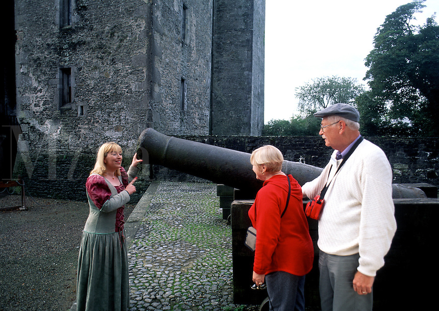 A retired tourist couple and costumed Irish tour guide look at a cannon at Bunratty Castle. Ennis, Ireland.