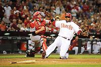 May 13, 2009; Phoenix, AZ, USA; Arizona Diamondbacks base runner Justin Upton slides safely into home ahead of the tag by Cincinnati Reds catcher Ryan Hanigan in the sixth inning at Chase Field. Mandatory Credit: Mark J. Rebilas-