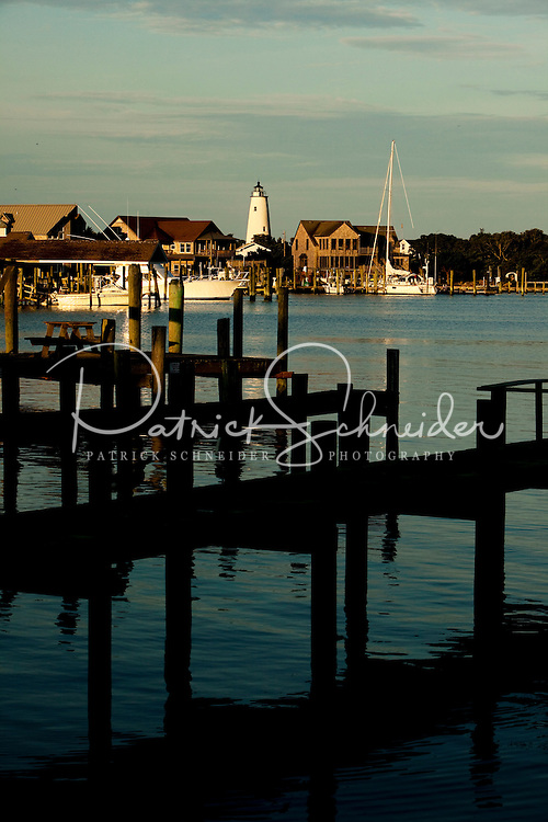 Piers and fishing docks in Silver Lake Harbor off Pamlico Sound make an attractive and romantic foreground to the Ocracoke Lighthouse. Ocracoke Light remains among the oldest lighthouses still active on the southern coast of North Carolina's Outer Banks, and it is the second oldest operating lighthouse in the United States (the first is Sandy Hook Light house in New Jersey). The first Ocracoke Lighthouse was built in 1803 on Shell Castle Island inside the Ocracoke Inlet not far from Blackbeard's hideout. Destroyed by lightning in 1818 it was replaced by the current light in 1823 on the banks of the inlet near Ocracoke Village. The white-brick conical lighthouse stands 75 feet tall and has 220 stairs to its top, though visitors are not allowed to climb. Ocracoke Island can only be reached by ferry. Charlotte NC photographer Patrick Schneider has extensive photo collections of the following lighthouses: Bodie Island Lighthouse, Bald Head Island Lighthouse, Cape Fear Lighthouse, Cape Hatteras Lighthouse, Cape Lookout Lighthouse, Currituck Beach Lighthouse, Diamond Shoal Lighthouse, Federal Point Lighthouse, Oak Island Lighthouse, and Ocracoke Lighthouse on Ocracoke Island.