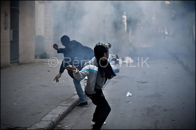 © Remi OCHLIK/IP3 - Tunis the 14 january 2011 - Young Tunisians protestor throw rocks to the anti riot police..Tunisia riots continued as President Zine El Abidine Ben Ali decided to dismiss his government following massive riots. The country's state news agency TAP says the president plans to call for new election in the next six months. Thousands of protestors took to the streets. The riots were sparked by high unemployment rates and a sagging economy as well as anger over government corruption. Tunisians enjoy little freedoms under President Zine El Abidine Ben Ali who has ruled a repressive regime for 23 years. Protestors ransacked buildings and threw rocks. Police used tear gas and gunshots to quell the crowd as protests got increasingly violent.