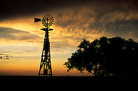 An old windmill is silhouetted by a dramatic sunset in the Texas Panhandle after a day of severe storms.