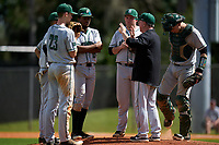 Dartmouth Big Green head coach Bob Whalen talks with Connor Bertsch (23), Bryce Daniel (4), Blake Crossing (13), Michael Calamari (3), and Ben Rice (9) during a game against the Omaha Mavericks on February 23, 2020 at North Charlotte Regional Park in Port Charlotte, Florida.  Dartmouth defeated Omaha 8-1.  (Mike Janes/Four Seam Images)