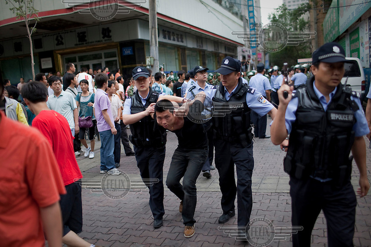 A policeman arrests a Han Chinese man who was part of a mob that chased down a Uighur in Urumqi. They caught up with the Uighur and beat him before the police intervened firing shots in the air and arresting the two Han attackers. The mob then attacked the police to try and stop the arrests. Ethnic violence between the Uighur and Han people had erupted in the city a few days earlier.