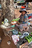 Cambodia.  Market near Siem Reap.  Man Selling Cooked Bananas.