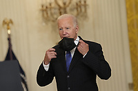 United States President Joe Biden removes his mask as he arrives to deliver remarks after meeting with senior officials and stakeholders to discuss collective efforts to address global transportation supply chain bottlenecks in the East Room of the White House in Washington, DC on Wednesday, October 13, 2021.<br /> Credit: Chris Kleponis / Pool via CNP /MediaPunch