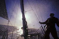 Sailor in the salt spray of waves aboard cruising sailboat, channel crossing, Kauai to Oahu